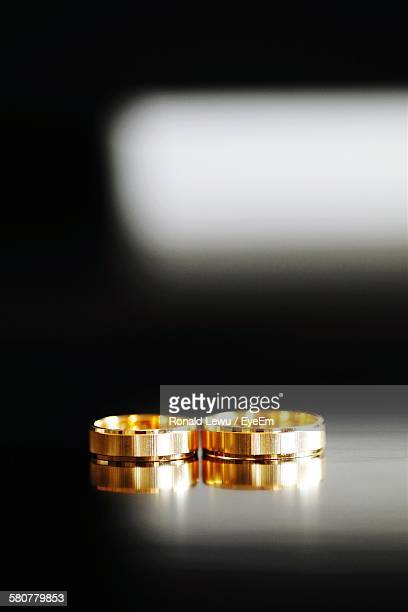 Close-Up Of Gold Wedding Rings On Table