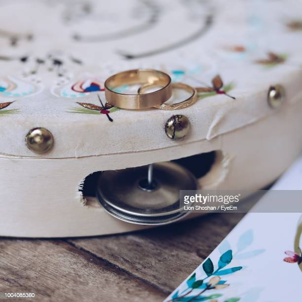 close-up of gold wedding rings on tambourine - tambourine stock photos and pictures