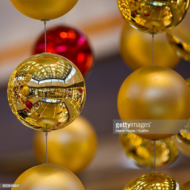 Close-Up Of Golden Ball Decorations Hanging In Mall