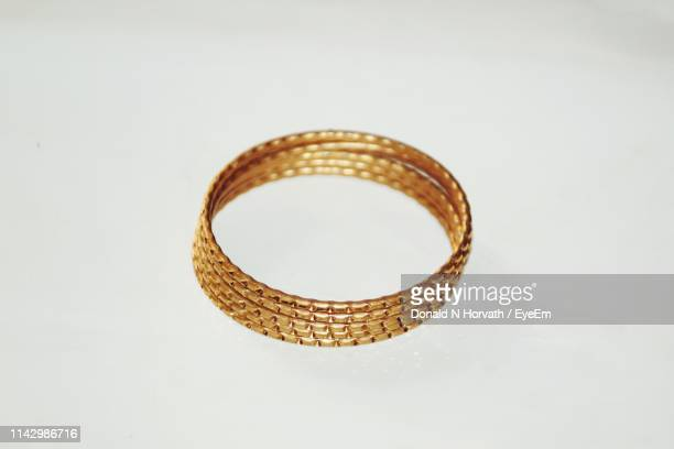 close-up of golden bangles on gray background - バングル ストックフォトと画像