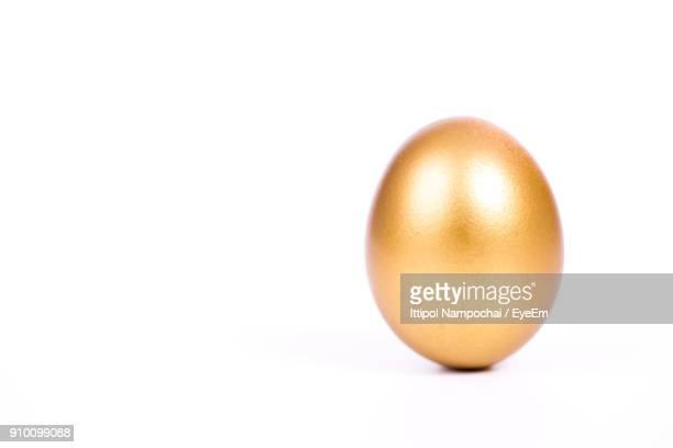 Close-Up Of Golden Egg On White Background