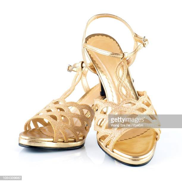 Close-Up Of Golden High Heels Over White Background