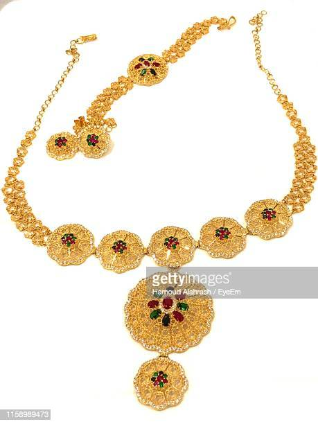close-up of golden jewelries over white background - necklace stock pictures, royalty-free photos & images