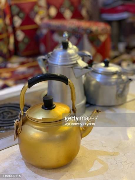 close-up of golden kettle on table - やかん ストックフォトと画像