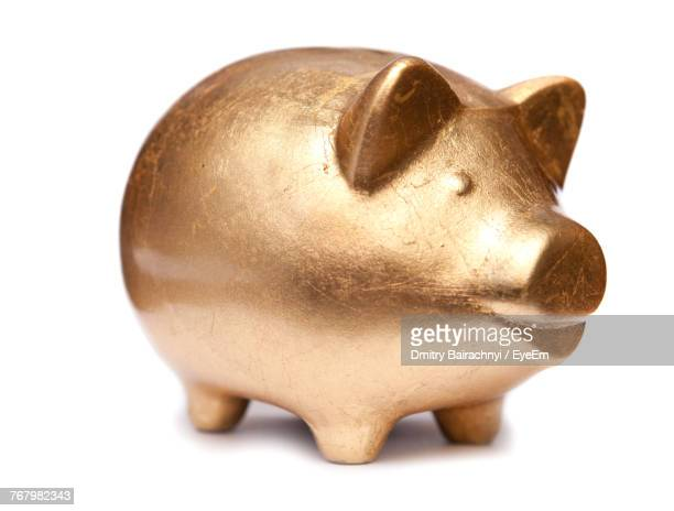 close-up of golden piggy bank over white background - piggy bank stock photos and pictures