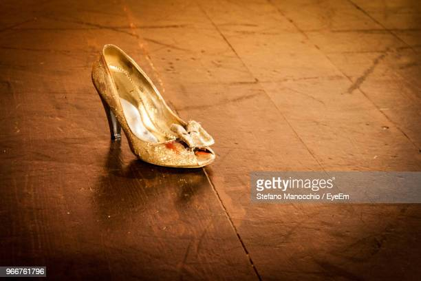 close-up of golden shoe on hardwood floor - gold shoe stock pictures, royalty-free photos & images