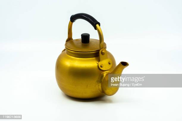 close-up of golden teapot against white background - やかん ストックフォトと画像