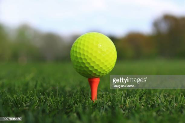 close-up of golf ball on a driving tee - teeing off stock pictures, royalty-free photos & images
