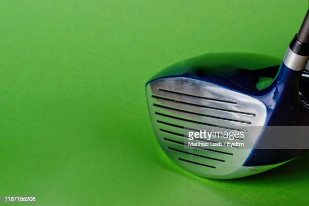 close-up of golf club against green background - driver golf club stock pictures, royalty-free photos & images