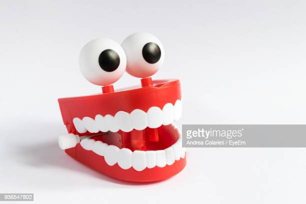 close-up of googly eyes and dentures over white background - googly eyes stock pictures, royalty-free photos & images