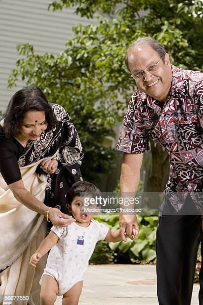 Close-up of grandparents walking with their grandson
