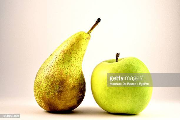 Close-Up Of Granny Smith Apple And Pear Against White Background