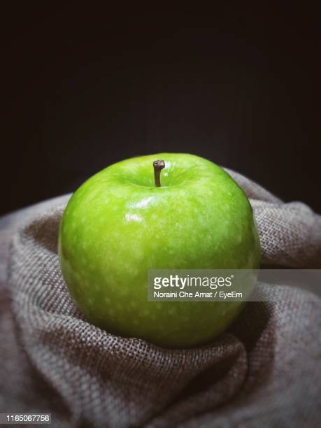 close-up of granny smith apple on burlap - frische stockfoto's en -beelden