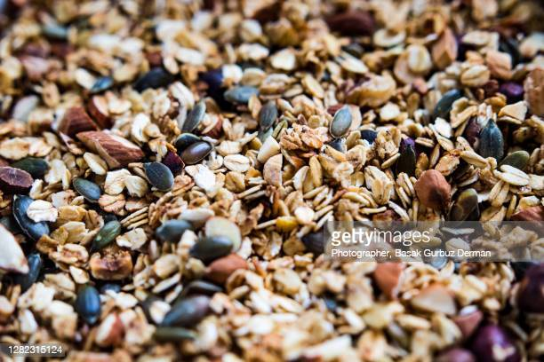 close-up of granola with clusters of wholegrain oats, seeds, and nuts - granola stock pictures, royalty-free photos & images