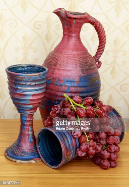 Close-Up Of Grapes And Potteries On Table