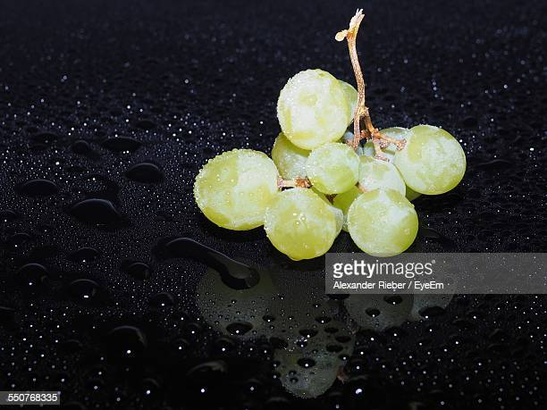 Close-Up Of Grapes Over Black Surface