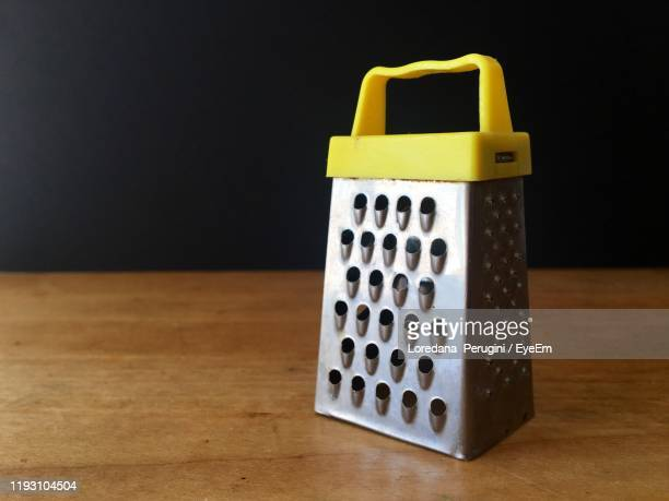 close-up of grater on table against black background - loredana perugini fotografías e imágenes de stock