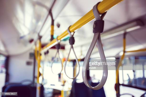 close-up of gray handles in empty bus - strap stock pictures, royalty-free photos & images