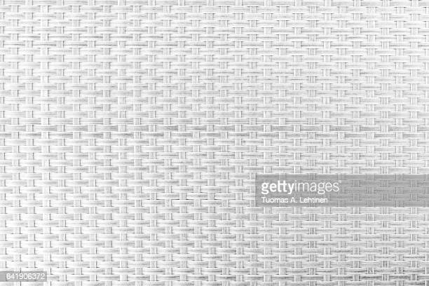 Close-up of gray plastic weave as woven background texture or pattern in black&white.