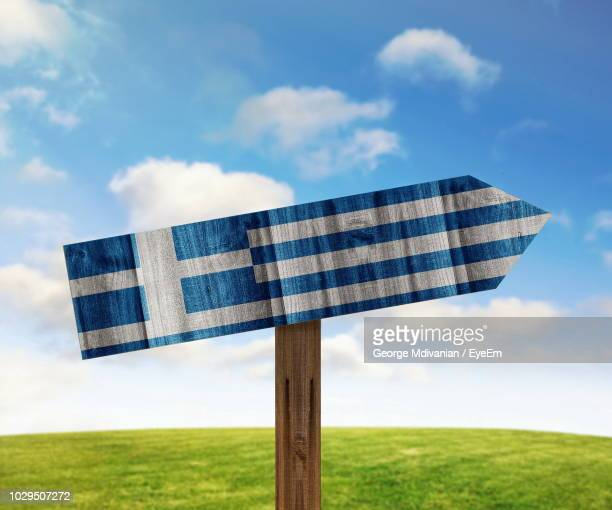 close-up of greek flag painted on wooden sign against sky - greek flag stock pictures, royalty-free photos & images
