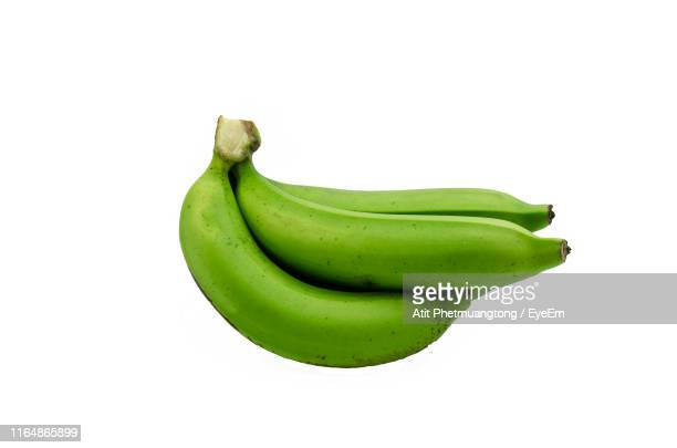 close-up of green bananas against white background - unripe stock pictures, royalty-free photos & images