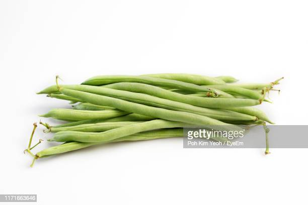 close-up of green beans against white background - green bean stock pictures, royalty-free photos & images