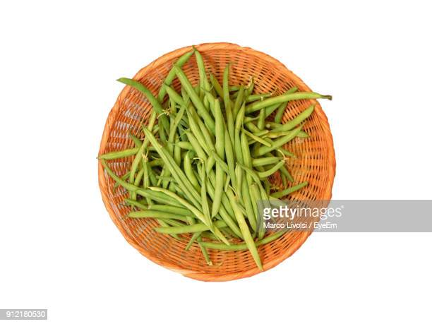 Close-Up Of Green Beans In Basket Against White Background