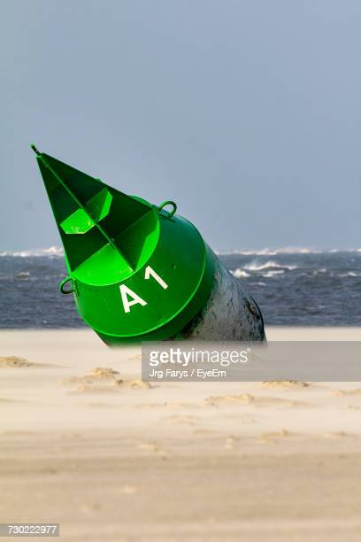 Close-Up Of Green Boat On Beach Against Sky