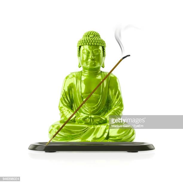 close-up of green buddha with incense stick over white background - incense stock photos and pictures