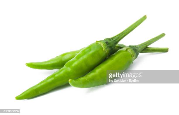close-up of green chili pepper against white background - green chili pepper stock pictures, royalty-free photos & images