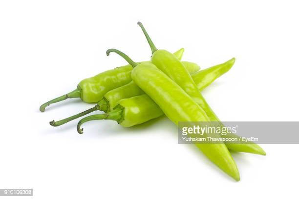 close-up of green chili peppers against white background - green chili pepper stock pictures, royalty-free photos & images