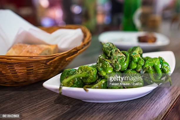 close-up of green chili peppers in plate on table - tapas stock photos and pictures