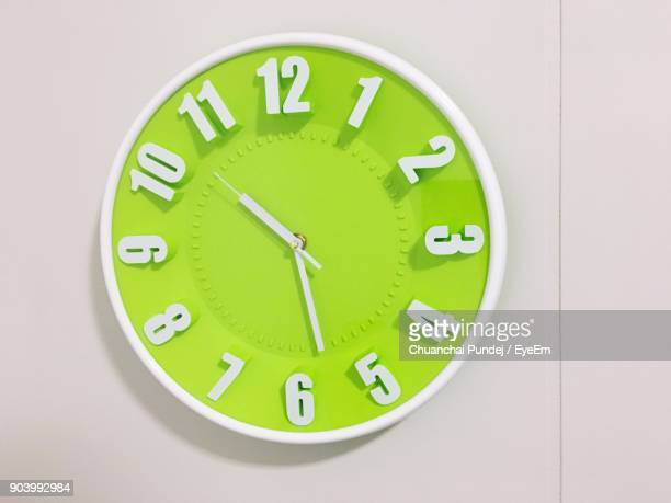 close-up of green clock on wall - cadran d'horloge photos et images de collection