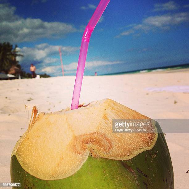 Close-Up Of Green Coconut With Drinking Straw At Beach