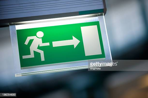 close-up of green emergency exit light sign - escapism stock pictures, royalty-free photos & images
