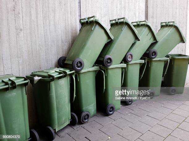Close-Up Of Green Garbage Cans Against Wall