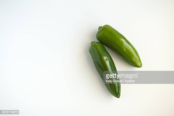close-up of green jalapeno peppers on white background - jalapeno stock-fotos und bilder