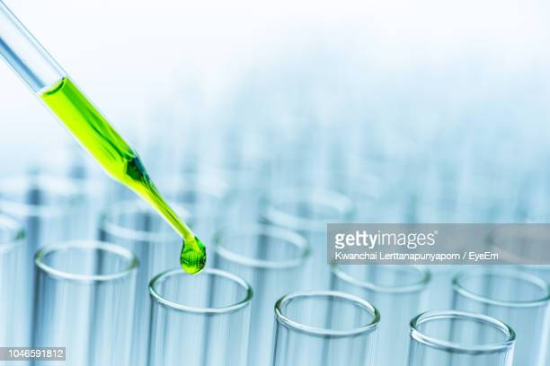 close-up of green liquid pouring from pipette in test tubes - place of research stock pictures, royalty-free photos & images