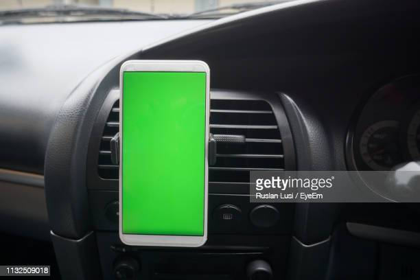 close-up of green mobile phone in car - dashboard stock pictures, royalty-free photos & images