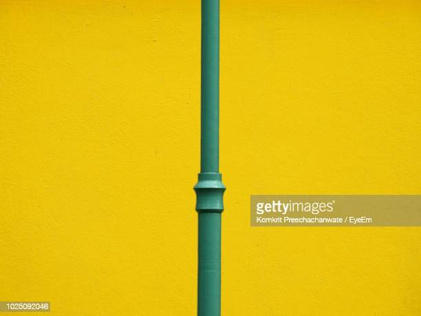 Close-Up Of Green Pole Against Yellow Wall