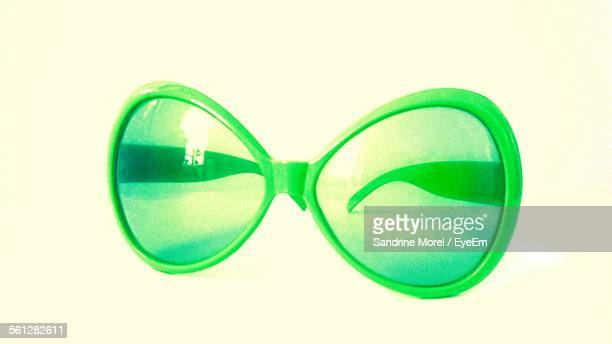 Close-Up Of Green Sunglasses Against White Background
