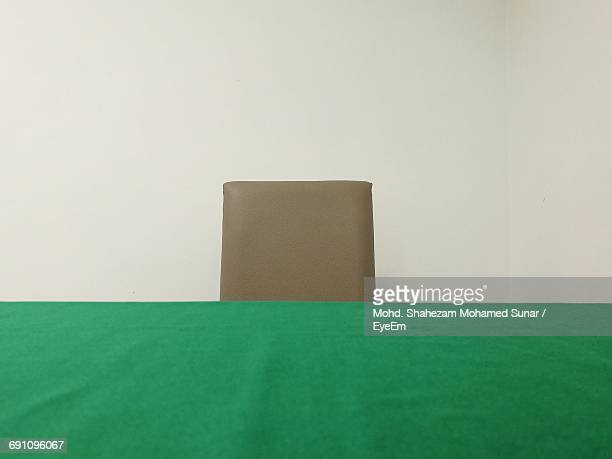 Close-Up Of Green Tablecloth By Chair Against White Wall