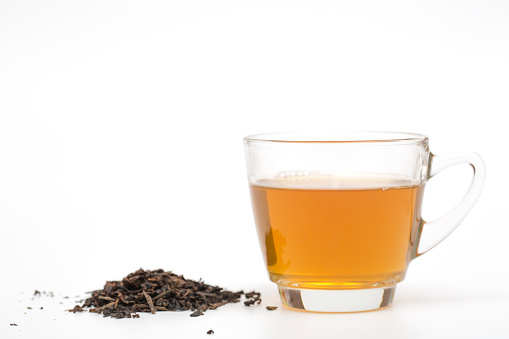 Close-Up Of Green Tea With Tea Leaves Against White Background - gettyimageskorea