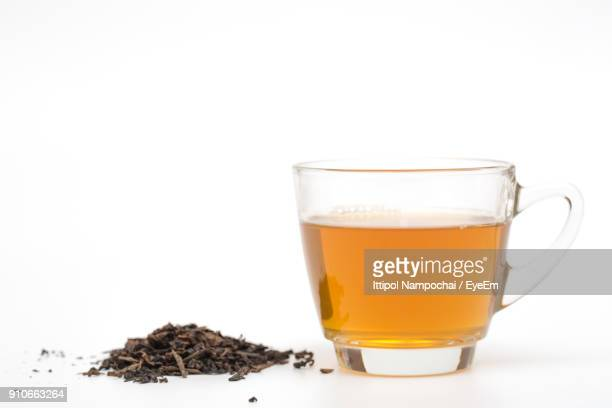 close-up of green tea with tea leaves against white background - tea leaves stock photos and pictures