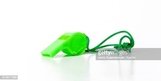 Close-Up Of Green Whistle Over White Background