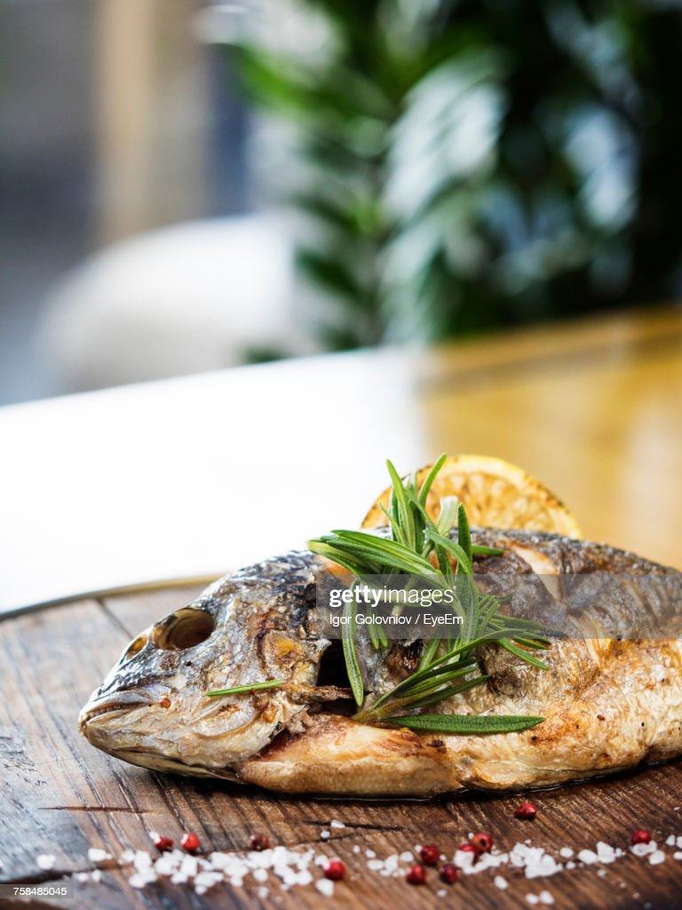 Close-Up Of Grilled Gilthead Bream Garnish With Herbs Served In Plate : Stock Photo