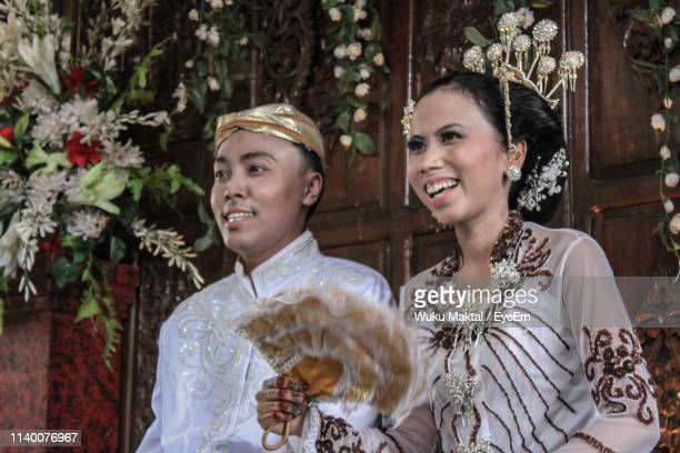 Close-Up Of Groom And Bride Looking Away