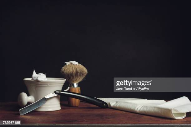 Close-Up Of Grooming Kit On Table Against Black Background
