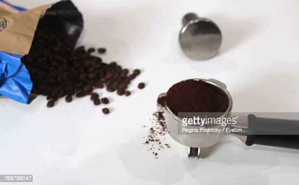 close-up of ground coffee in portafilter on white background - ground coffee stock photos and pictures