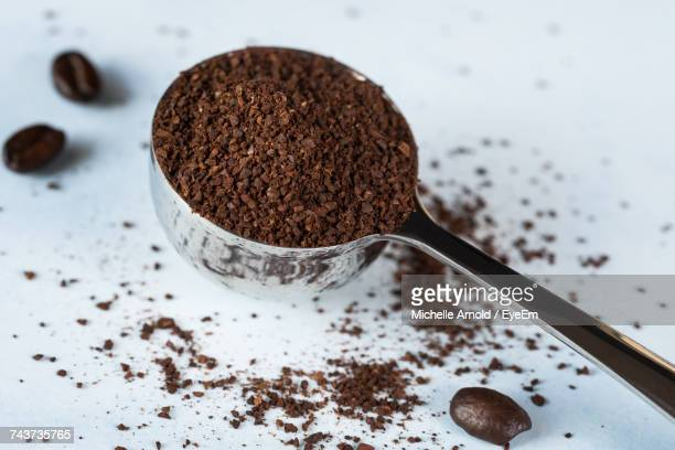 close-up of ground coffee in scoop on table - ground coffee stock photos and pictures
